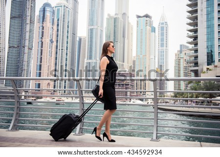 A beautiful woman walking around a city with her luggage. - stock photo
