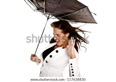 A beautiful woman wearing a white jacket holding a black umbrella in a strong wind on a white background. In the wind. - stock photo