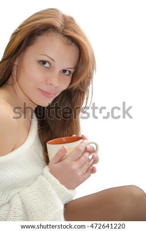 A beautiful woman with a cup of hot drink on a white background.