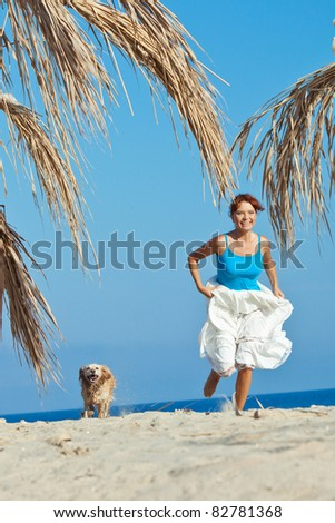 A beautiful woman with a playful young dog on nature - stock photo