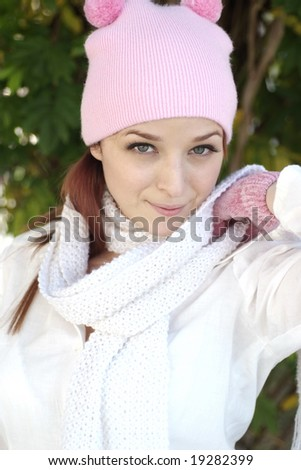 A beautiful woman with a red hair, white scarf, and pink bonnet and gloves.