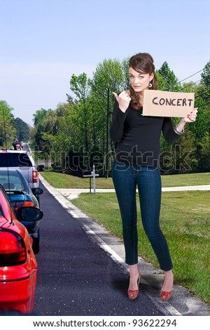 A beautiful woman with a sign hitch hiking to a concert - stock photo