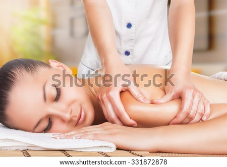 A beautiful woman with â??â??closed eyes getting a massage at the spa - stock photo