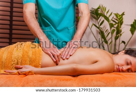 A beautiful woman with her �¢??�¢??eyes closed getting a massage at the spa