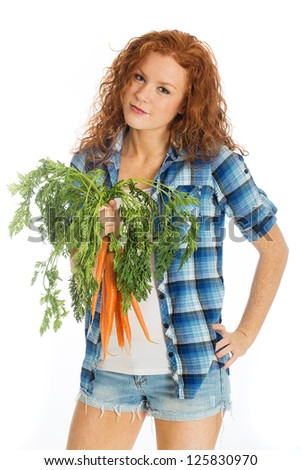 A beautiful woman with red hair and short denim shorts holding a batch of farm fresh carrots - stock photo