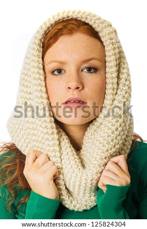 A beautiful woman with red hair, freckles and a warm scarf wrapped around her head. - stock photo