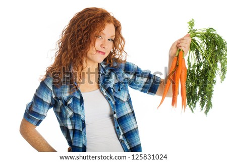 A beautiful woman with red hair holding a cluster of farm fresh carrots. - stock photo