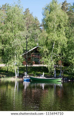 A beautiful wooden cottage in Finland on the shore of the lake. - stock photo