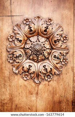 A beautiful wooden rose on a door in Tuscany Italy - stock photo
