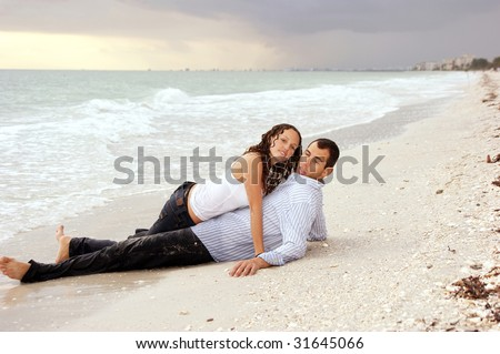 A beautiful you lady is laying on top of a man at the beach, their clothes are wet and she is looking at viewer, he has strange expression on his face at sunset. - stock photo
