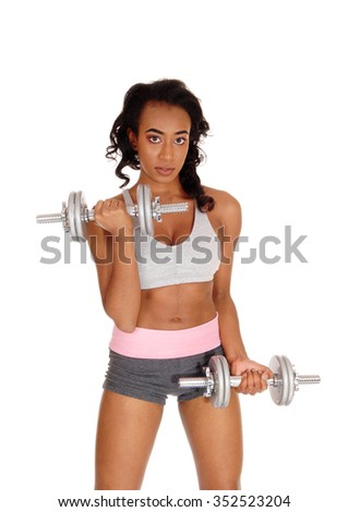 A beautiful young African American woman in a gray sports bra and shorts, exercising with dumbbell's, isolated for white background. - stock photo