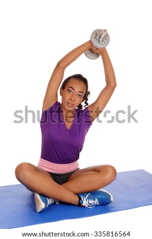 A beautiful young African American woman in a violet top and shorts, exercising with dumbbell's, isolated for white background. - stock photo