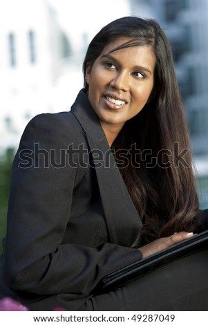 A beautiful young Asian businesswoman with a folder and a wonderful smile shot outside in golden sunshine