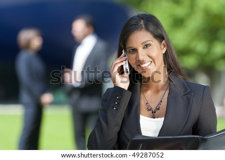A beautiful young Asian businesswoman with a wonderful smile chatting on her cell phone with her colleagues out of focus behind her. - stock photo