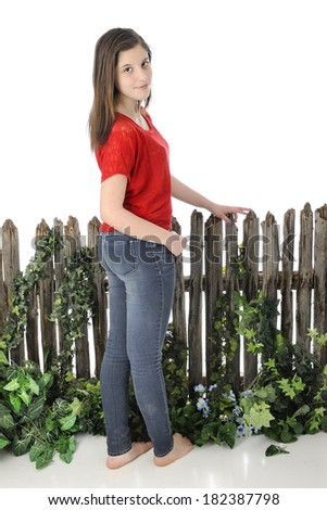 A beautiful young barefoot teen standing before an old vine-covered fence.  She's looking back at the viewer. On a white background. - stock photo