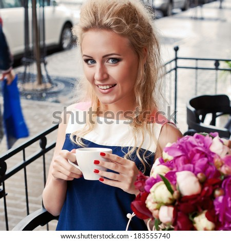 a beautiful young blond girl with blue eyes and toothy smile at the table in pavement cafe is holding a tea cup - stock photo