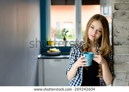 A beautiful young blond woman drinking coffee in the kitchen with blue cup. - stock photo