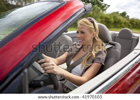 A beautiful young blond woman driving her convertible car in the sunshine.