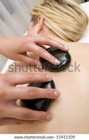 A beautiful young blond woman receives a hot stone massage from a beautician