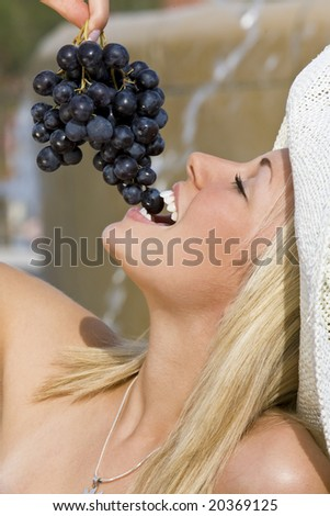 A beautiful young blond woman sitting in front of a fountain eating a bunch of black grapes - stock photo