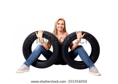 A beautiful young blond woman sitting with her legs through car tires. Isolated on white background. - stock photo