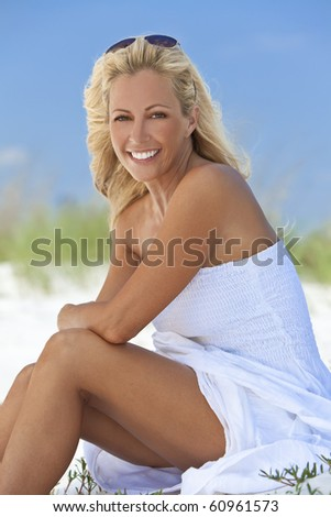 A beautiful young blond woman smiling in a white sundress sitting on a deserted tropical beach