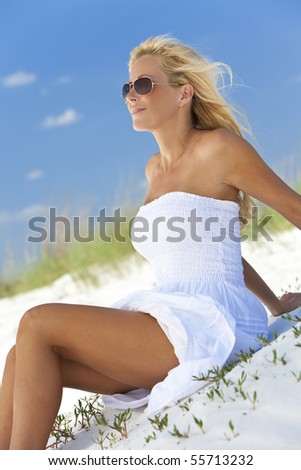 A beautiful young blond woman smiling in aviator sunglasses and a white sundress sitting on a deserted tropical beach - stock photo