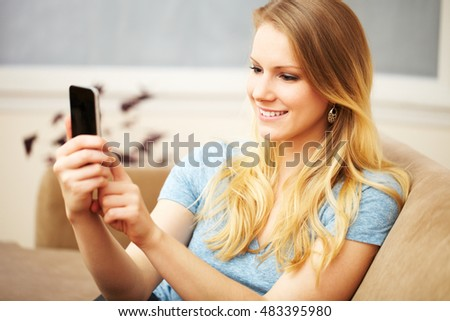 A beautiful young blond woman smiling sitting on a sofa on her smart phone.