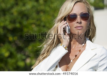 A beautiful young blond woman wearing aviator sunglasses and a white suit talking on her cell phone in a sunny location