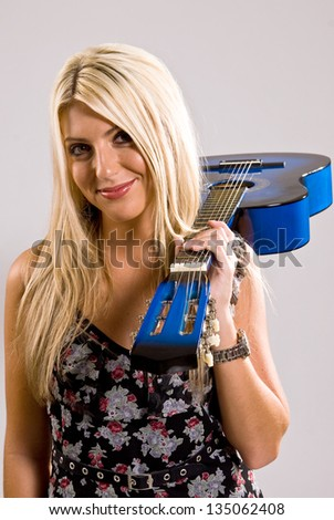 A beautiful young, blonde, female holding a blue guitar over her shoulder in a floral print dress with a smile on her face. - stock photo