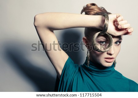 a beautiful young blonde in blue dress wearing wristbands over gray background. studio shot - stock photo