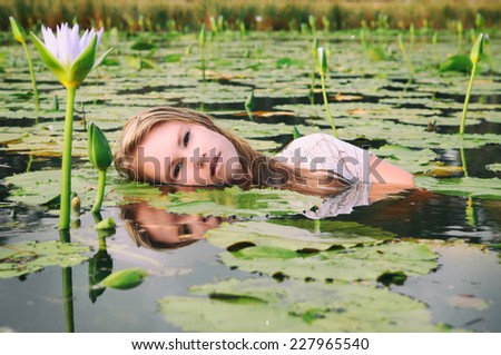 A beautiful young blonde lady is floating amongst the purple lillies in a pond or lake in an artistic setting. Filtered images. - stock photo