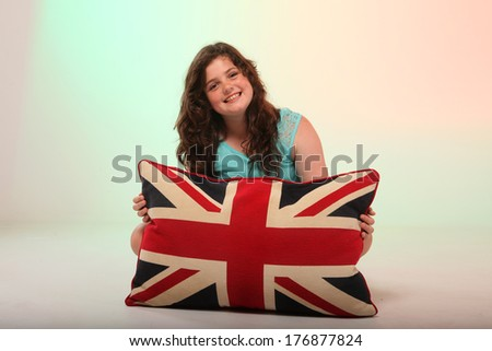A beautiful young brunette girl is hugging her pillow with the union jack colors on it.