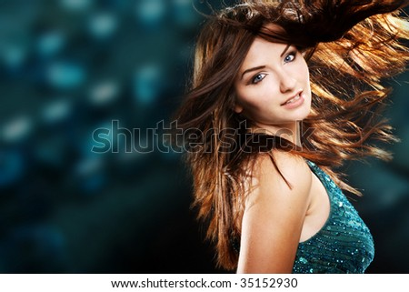 A beautiful young brunette woman dancing with her hair in motion in a nightclub scene.
