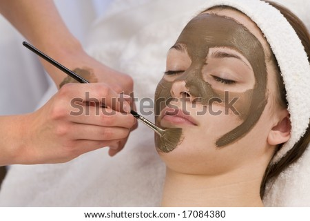 A beautiful young brunette woman having a chocolate face mask applied by a beautician