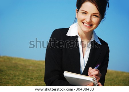 A beautiful young business woman in a field with a blue sky writing on a notepad.