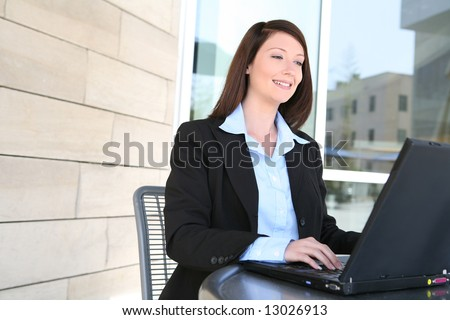 A beautiful young business woman on laptop at office building - stock photo