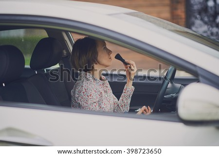 A beautiful young Caucasian woman doing make-up on the front seat of the car - stock photo