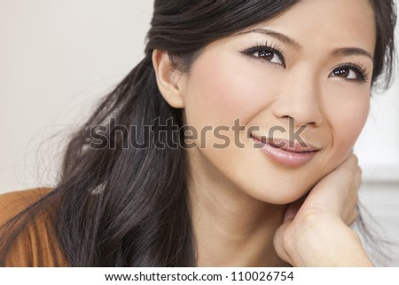 A beautiful young Chinese Asian Oriental woman resting on her hand with a wonderful smile - stock photo