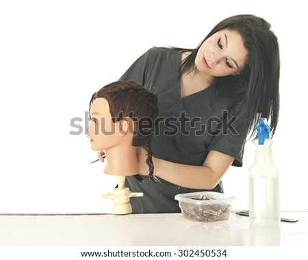 A beautiful young cosmetology student leaning to check the braided hair she's been styling on her practice mannequin's head.  On a white background with space on the left for your text. - stock photo