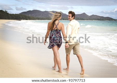A beautiful young couple go for a walk on the beach in Hawaii - stock photo