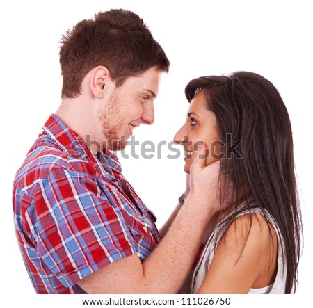 A beautiful young couple smiling at each other while he holds her tenderly - stock photo
