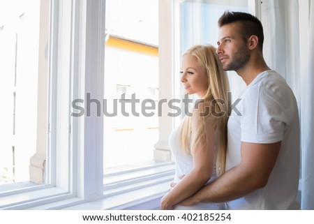 A beautiful young couple standing at the window at home.
