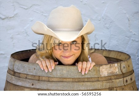 A beautiful young cowgirl peeks out of a barrel, looking like she has a secret. - stock photo