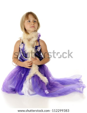 A beautiful young elementary girl playing dress-up in a fancy purple dress, necklace, bracelets and a boa.  On a white background.