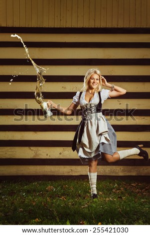 A beautiful young german girl in dirndl clothing is holding a jug of beer. - stock photo