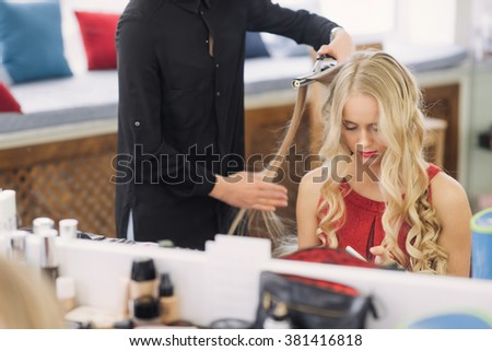 a beautiful young girl, frizz hair until she looks in the phone - stock photo