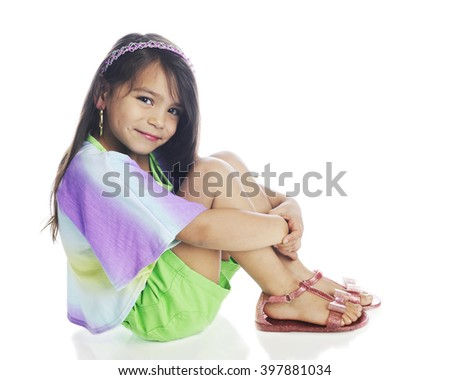 A beautiful young girl happily looking at the viewer while sitting pretty in her shorts, multicolored shirt and sandals.  On a white background. - stock photo