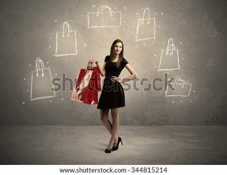 A beautiful young girl in black standing with red shopping bags in front of brown background wall and drawing illustration concept - stock photo