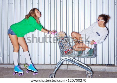 a beautiful young girl in sexy shorts, stockings and roller skates is showing out her tongue to a beautiful girl in a supermarket trolley - stock photo